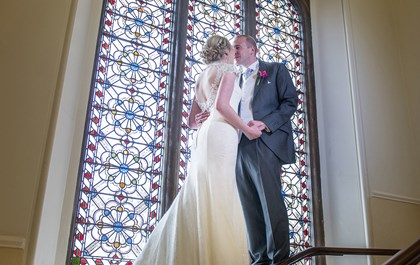 Wedding couple standing by the stained glass window